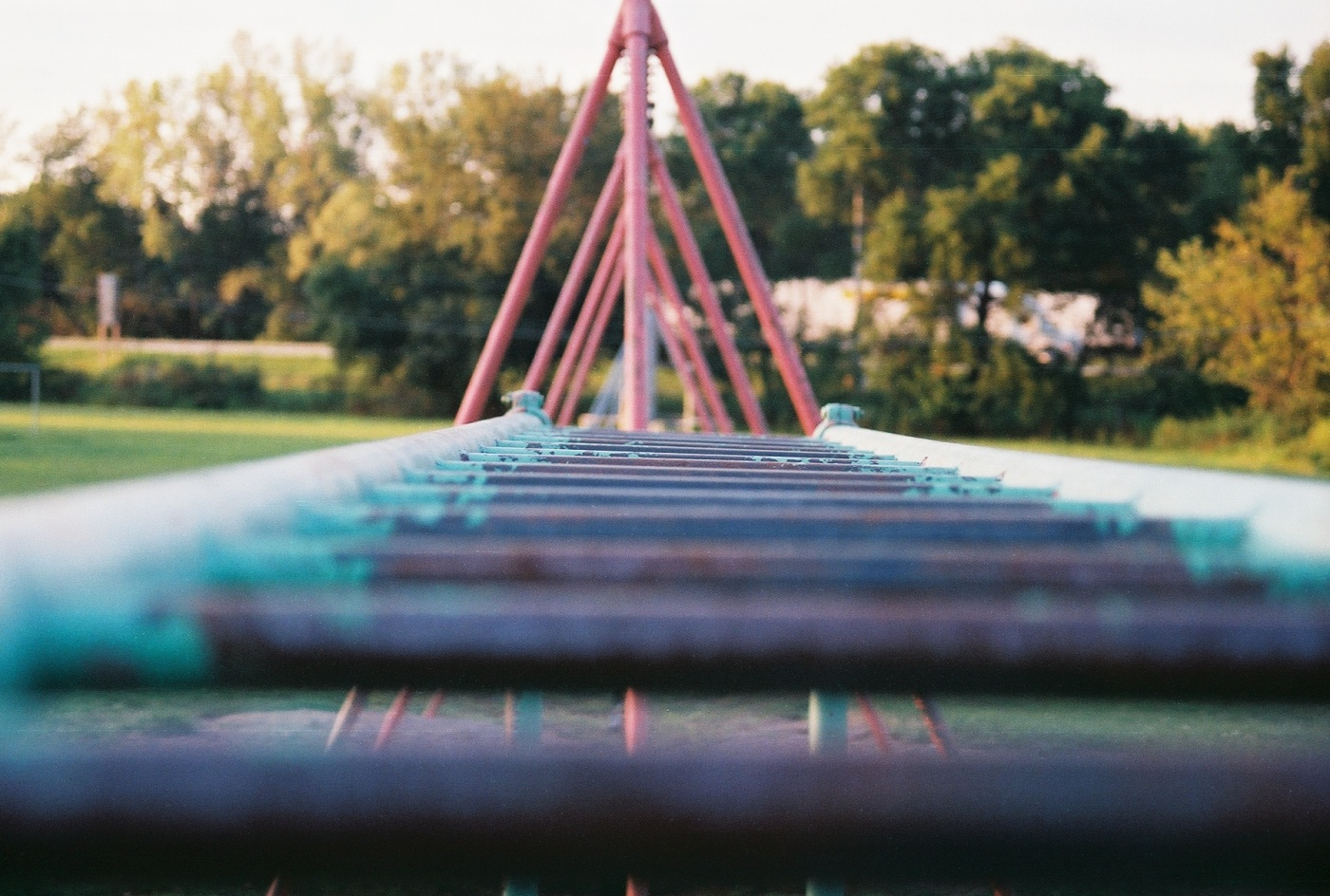 Photo looking across the top of monkey bars in a playground