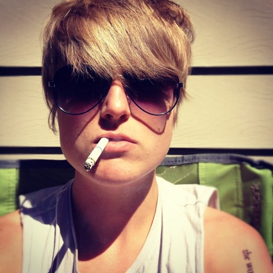 Woman with short hair and sunglasses smoking